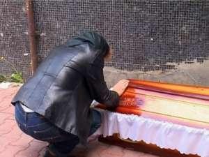 Mama lui Eugen Ursariu plângându-şi fiul lângă sicriu